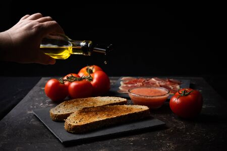 hand pouring oil on toast with ham and tomato. Mediterranean breakfast, Spanish cuisine