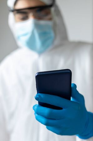 doctor with latex gloves and coronavirus protective clothing looking at the mobile phone