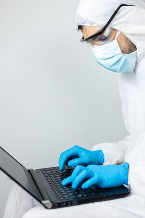 researcher working with his laptop in covid-19 coronavirus protective clothing