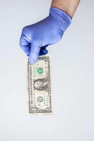 blue latex gloved hand holding dollar bill. Concept financial crisis coronavirus, covid-19