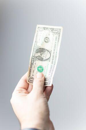 hand offering a US dollar bill