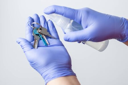 gloved hands disinfecting a set of keys, to prevent the spread of the coronavirus Reklamní fotografie