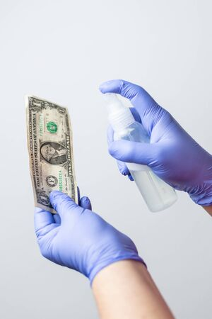 gloved hands disinfecting a US dollar bill with alcohol spray, to prevent the spread of the coronavirus