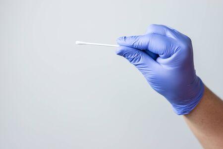 blue gloved hand holding coronavirus nasal test stick, or covid-19. Coronavirus test concept.