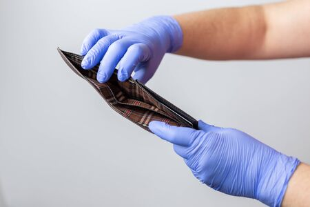 two hands with blue gloves showing an empty wallet. Concept of financial crisis due to the coronavirus pandemic.