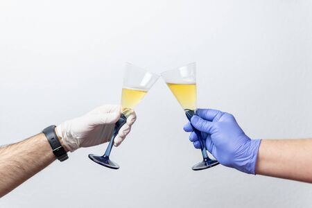human hands with protective gloves toast with two cups. Concept of the end of the coronavirus crisis, covid 19 Reklamní fotografie