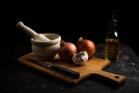 cooking scene with mortar, garlic, onions, knife and cutting board. Dark food style Reklamní fotografie