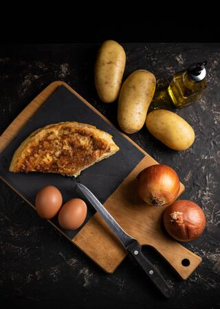 potato omelette with its ingredients. Typical Spanish dish, seen from above. Dark food style