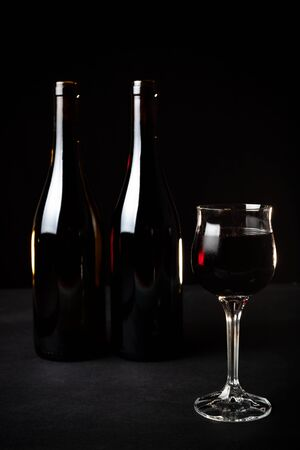 bottle of red wine, bottle of white wine, and glass on a black background