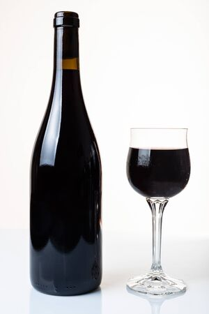 bottle of red wine and glass isolated on a white background