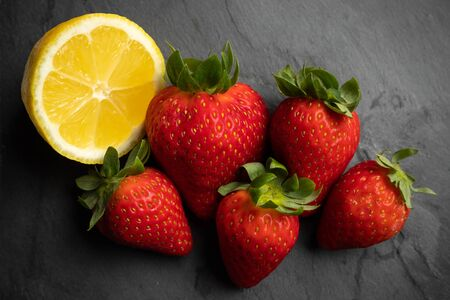 five strawberries with lemon on a black stone background, dark food photography