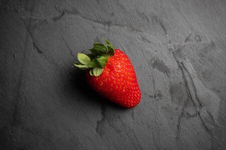 One strawberry on a black stone background, dark food photography Reklamní fotografie