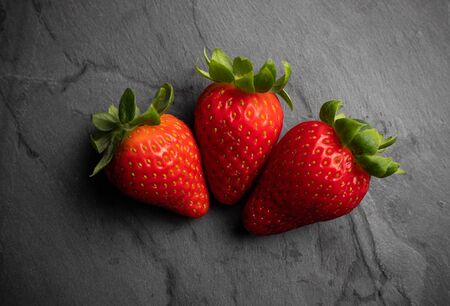 strawberries on a black stone background, dark food photography Reklamní fotografie