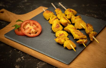 Moorish skewers on black stone and wooden cutting board with tomato slices Reklamní fotografie