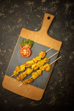 Moorish skewers on black stone and wooden cutting board with tomato slices