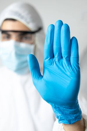 doctor with coronavirus protective clothing asking to stop the pandemic. stay at home
