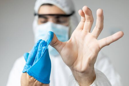 doctor with coronavirus protective clothing showing the correct way to remove the gloves Reklamní fotografie