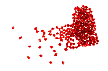 delusion: Red broken heart shape made of pomegranate seeds on white background
