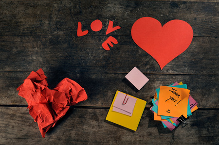 Handmade hearts and blank customizable post its on a vintage wooden table  photo