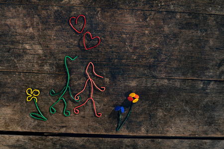 Creative love story, couple in love, hearts and flowers made from paper clips and thumbtacks on a beautiful wooden background  photo