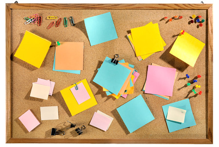Editable blank paper notes and office supplies  paper clips, pins, thumbtacks  on cork message board  photo