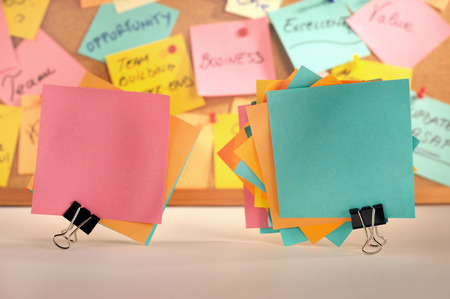 Groups of standing paper notes fastened with paper clips, cork message board in the background  photo