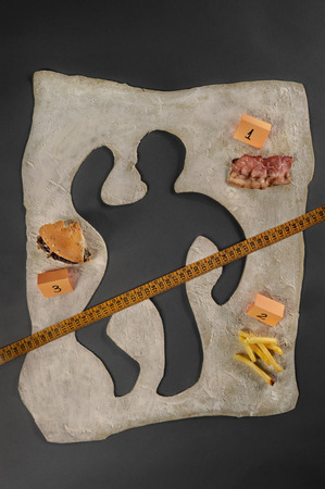 Unhealthy food victim  Crime scene, a silhouette of a man made out of baking dough  Next to the victim s silhouette there are several evidences about the cause of death, a piece of bacon, a hamburger, fries, a measuring tape  photo