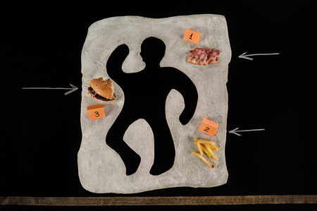 Unhealthy food victim  Crime scene, a silhouette of a man made out of baking dough  Next to the victim s silhouette there are several evidences about the cause of death, a piece of bacon, a hamburger,fries, a measuring tape   Archivio Fotografico