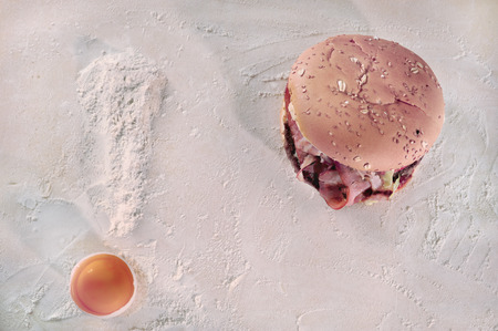 Weight loss concept, exclamation mark made out of natural ingredients  flour and an egg  next to a hamburger  photo