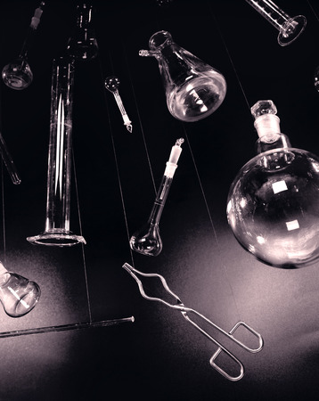 Creative and vintage setup, laboratory glassware and equipment hanged over blackboard background  Image suitable for background use