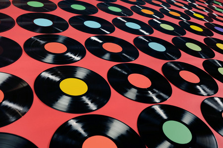 Music - Vinyl records  Colorful collection of vinyl records, LPs, on red background, angle view  The labels can be easily customized, the image is suitable for background use