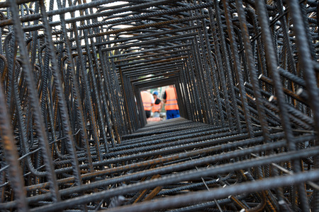 worksite: professional workers seen through steel bars reinforcement on a construction site. Workers wearing uniforms and helmets seen through steel bars reinforcement on a worksite.