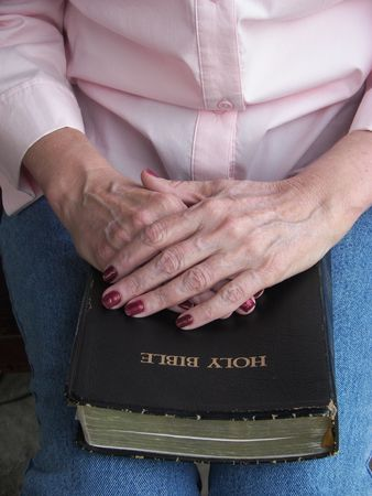 Senior with Hands Resting on a Bible
