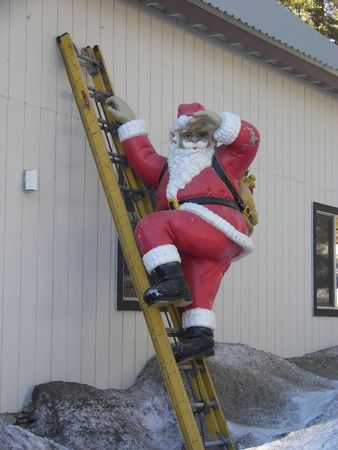 Santa climbing a ladder Standard-Bild