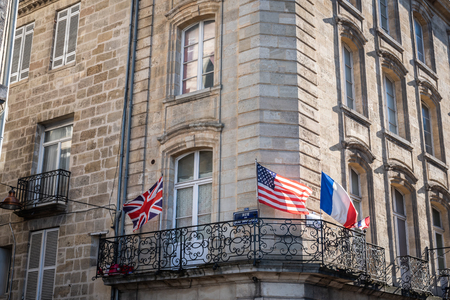 French, American and English flags on the balcony of a Bordelais building in Bordeaux
