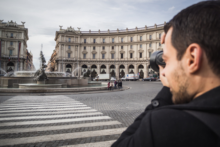 ROME, ITALY - NOVEMBER 16, 2017: Photographer photographing Piazza Della Repubblica in Rome with people leaning around