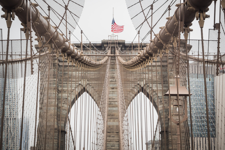 Details of the Brooklyn Bridge Architecture with the American Flag Floating at the Top of the Arch, New York