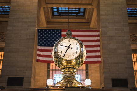 10:35 am at the famous Grand Golden Clock in Grand Central New York with the American flag in the background