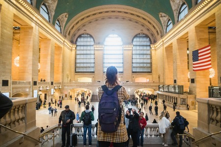NEW YORK,USA - FEBRUARY 24, 2018: Tourist taking a photo of Grand Central Station in New York among the crowd Редакционное