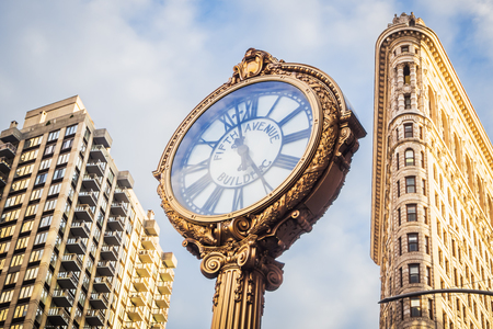 The iconic golden clock of Flatiron Building in Midtown Manhattan on a beautiful blue sky in NYC Imagens