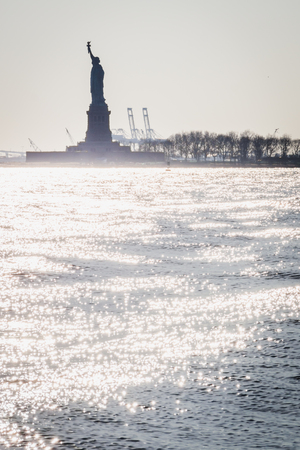 Statue of Liberty shape against the light from Lower Manhattan in New York