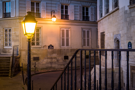 Cityscape of a passage in an old Parisian street before sunrise on the Ile of the Cite in Paris France Фото со стока