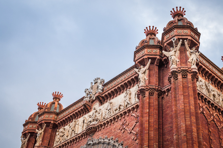 Architectural close-up of the top of the monumental red brick Arch of Barcelona in Spain 스톡 콘텐츠