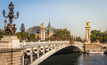 The magnificent Alexandre III bridge over the Seine River with the Grand Palais in the background in summer in Paris