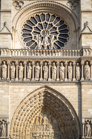 Famous rose window and statues in front of the main entrance of the Notre Dame cathedral in Paris 写真素材