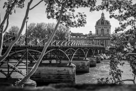 Vintage black and white photo of the Pont des Arts over the Seine river under a summer sky in Paris
