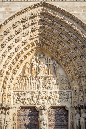 Architectural details of the arch above the main entrance of the Notre Dame de Paris cathedral