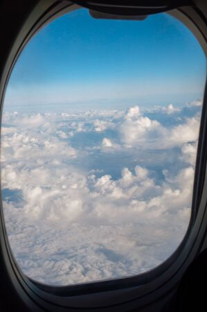 Altitude travel above the clouds through the porthole of an airplane