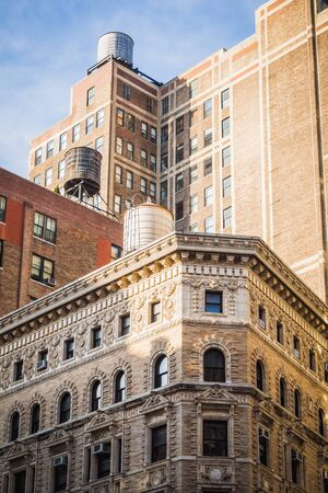 Water towers over buildings of different eras in New York on a sunny day Imagens