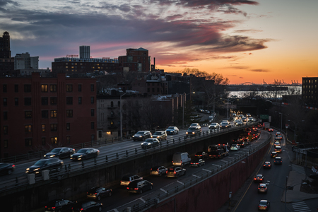 Colorful sunset on the Brooklyn Queens Expy highway between Brooklyn and Manhattan in NY Banco de Imagens - 124999211